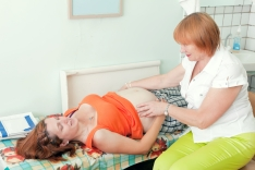 midwife examining pregnant woman in clinic